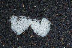 Riz noir et forme blanche de coeur Image stock