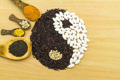 Riz noir et pilule blanche formant un symbole de yang de yin Photos stock