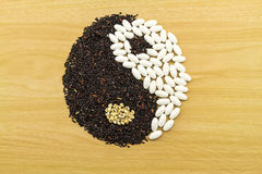 Riz noir et pilule blanche formant un symbole de yang de yin sur l'OE brun Photographie stock