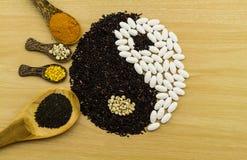 Riz noir et pilule blanche formant un symbole et un turme de yang de yin Photo stock