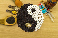 Riz noir et pilule blanche formant un symbole et un turmer de yang de yin Images stock