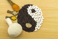 Riz noir et pilule blanche formant un symbole et une station thermale de yang de yin de fines herbes Image libre de droits