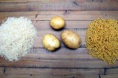 Riz, pommes de terre et pâtes de macaronis sur une table en bois Trois hydrates de carbone communs qui fournissent l'énergie mais photo libre de droits