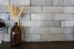 Riz sec dans la bouteille avec le fond de brique et l'espace de copie pour le texte Photographie stock libre de droits