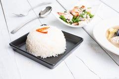Riz thaïlandais cuit à la vapeur de jasmin dans le plat noir avec SA épicée de fougère de paco photo stock