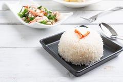 Riz thaïlandais cuit à la vapeur de jasmin dans le plat noir avec SA épicée de fougère de paco photographie stock