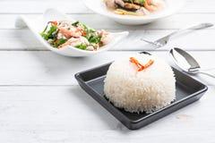 Riz thaïlandais cuit à la vapeur de jasmin dans le plat noir avec SA épicée de fougère de paco photos libres de droits