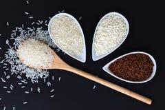 riz visqueux/collant du genre 3 de riz thaïlandais de jasmin de riz thaïlandais cru, riz brun dans des tasses blanches Photographie stock libre de droits