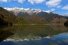 Riza lake, yellow autumn-green forest and white snow peaks. Caucasus. Abkhazia. Riza lake, yellow autumn-green forest and white snow peaks, reflecting in the Royalty Free Stock Images