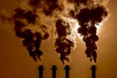 Rizos venenosos cáusticos negros del humo fuera de los tubos en el cielo de la puesta del sol Chimenea tóxica de los humos que in imagenes de archivo