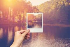 Ręka chwyta fotografii stawu natychmiastowa woda i wschód słońca Obraz Stock