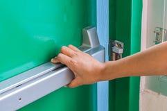 Ręka jest pchać/otwiera przeciwawaryjnego pożarniczego wyjścia drzwi Zdjęcia Stock