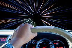 Ręka kierowcy mienia kierownica z abstrakcjonistycznym prędkość ruchu lekkich linii tłem Obraz Stock