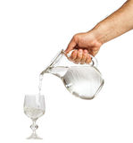 Ręka trzyma wodnego dzbanek i nalewa wodę w szklaną filiżankę Zdjęcia Royalty Free