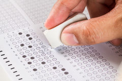 Ręka wymazuje źle odpowiedź na egzaminu węgla papieru komputeru prześcieradle Fotografia Royalty Free