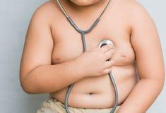 Ręki chłopiec czeka serce stetoskopem Obraz Royalty Free