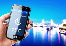 Ręki mienia smartphone z pogodą w Londyn Zdjęcie Stock