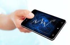 Ręki mienia telefon komórkowy z rynek papierów wartościowych mapą Zdjęcia Royalty Free