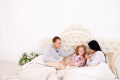 RKid girl ill, get cold mother wipes snot on bed. Women caring sick child, wiping nose with tissue. Child in bed with mom and dad. Young couple caring of their Stock Image