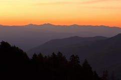 rökig soluppgång för stora berg Arkivfoto