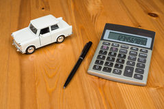 Räknemaskin, en penna och en leksakbil Royaltyfri Bild
