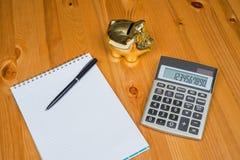 Räknemaskin med Piggybank och en notepad Arkivbilder