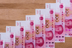 100 RMB notes positioned as rising stairs on wooden background. Stock Photos