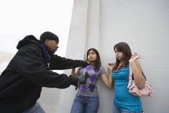 Rånare som skrämmer två unga flickor med kniven Fotografering för Bildbyråer
