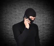 Rånare som talar på telefonen Arkivfoton