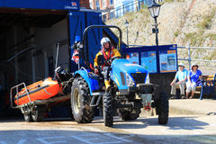 RNLI launching a rescue dingy. The Royal National lifeboat Institution at cromer, norfolk, England, UK. A tractor pulls a rescue dingy from the lifeboat station Royalty Free Stock Photo