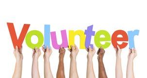 Różnorodne ręki Trzyma słowo wolontariusza Fotografia Royalty Free
