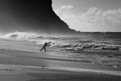RNP Fisherman BW. Pacific ocean stormy waves sand beach and dard cliff fisherman with rod against wind Royalty Free Stock Image