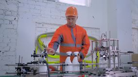 Roślina pracownika samiec w hełmie i coveralls kontroluje ilości produkcję gospodarstwo domowe substancje chemiczne na automatycz zbiory