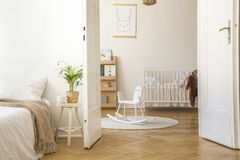 Roślina na stolec obok łóżka w białym sypialni wnętrzu z kołysać konia na dywaniku i kołysce fotografia royalty free