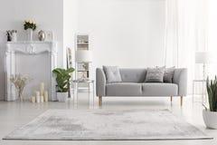 Rośliny i dywan w białym żywym izbowym wnętrzu z świeczkami obok popielatej leżanki Istna fotografia obrazy stock