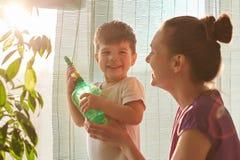Rośliny opieki pojęcie Rozochocona mała męska dzieciaków chwytów kiści butelka, chce nawadniać kwiatu, stoi jego czule macierzyst zdjęcia stock