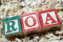 ROA return on assets acronym on wooden blocks. Return on assets acronym on wooden blocks business and financial terminologies stock photos