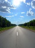 Road 1. A road continuing to infinity in a forest land and the shining white sun Stock Photo