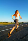 Road. The woman running on road against the sunset sun Royalty Free Stock Image