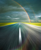 Road. Storm clouds with rainbow and asphalt road with reflection of rainbow Stock Images