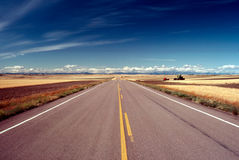 ROAD. In Montana , Harvest, empty  with visible harvest equipment on field Royalty Free Stock Photography