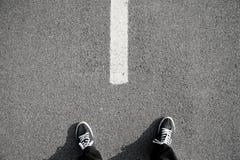 On the road. Closeup to man's feet on asphalt Royalty Free Stock Photos