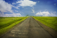 Road. Straight and beautiful old Road over mountain top with grass field on both sides Stock Photo