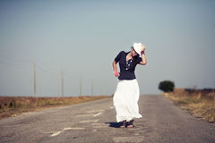 On the road. Woman in a white skirt and white hat on the open road stock photos