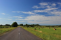 Road. Leaving afar across the field with oblique hay Stock Photo
