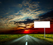 Road. Empty road through fields with blank road-sign Royalty Free Stock Photos