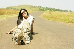 On the Road. An indian model posing, sitting on the road Royalty Free Stock Photography