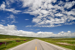 On the road. Which straight leads to the far-far-away under the blue sky Stock Photography