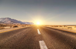 Road. In the desert and sunset Stock Photos