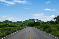 Road. Mountain roads signs sky green grass and clouds Royalty Free Stock Image
